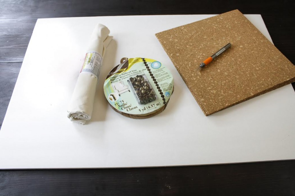 Assemble the materials you need: A piece of fabric, foam core board, cork tiles, nailhead trim , Mod Podge, an office stapler, scissors and a craft knife.