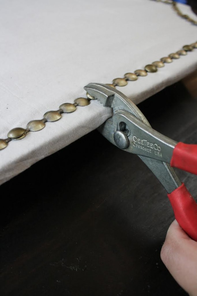 Use wire cutters to secure the nail head trim to the cork board.