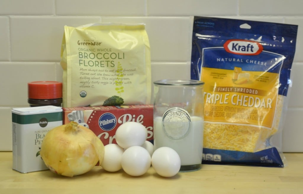 Assemble the veggie quiche ingredients: eggs, cheese, broccoli, pie crust and seasonings.