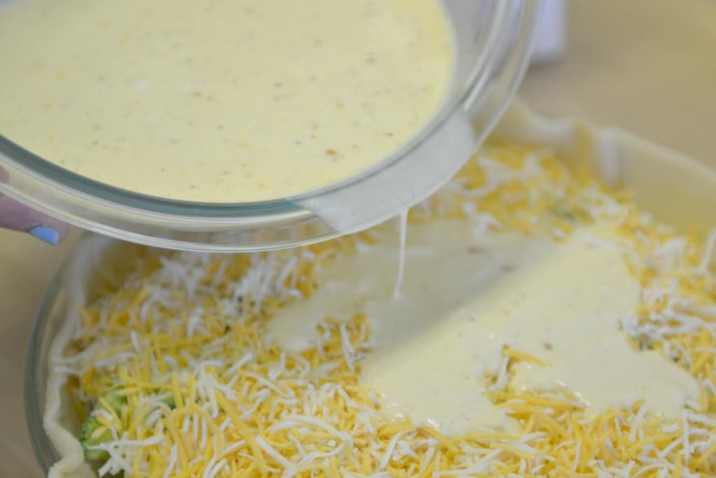 Pour the egg and cream mixture over the top of your shredded cheese and vegetables.