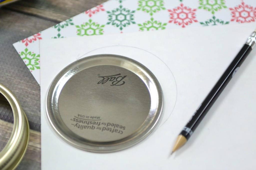 Step one is to trace the lid of the mason jar on the gift paper you'll be using to label the jar.