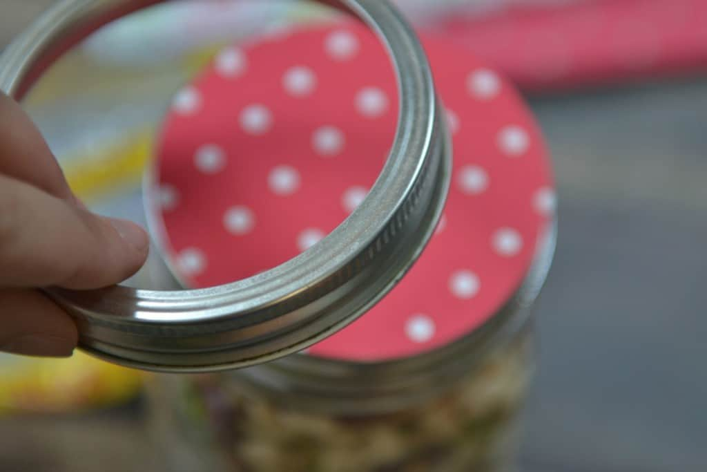 Seal the mason jar after inserting the circle of decorative paper on the top of the lid.