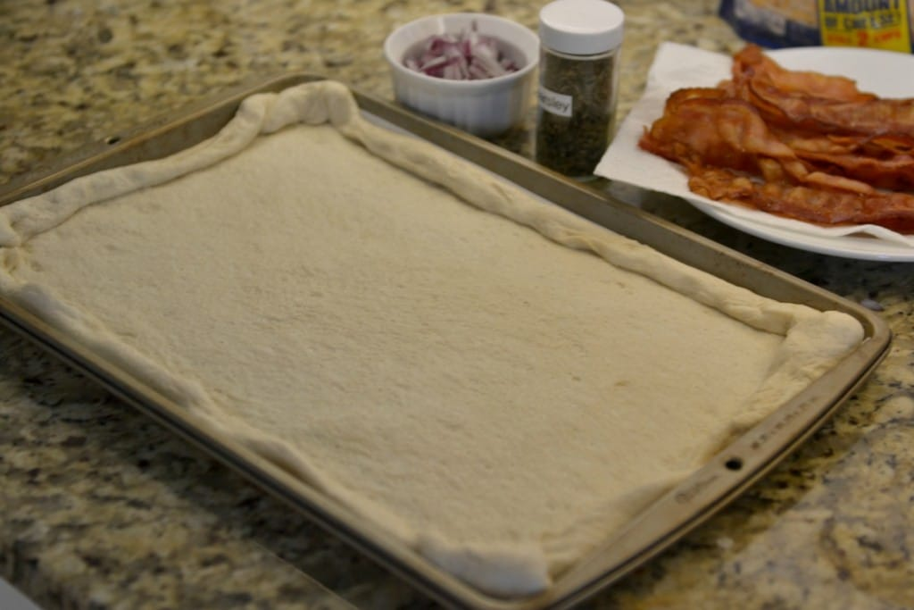 Unroll pizza crust onto parchment paper covered cookie sheet.
