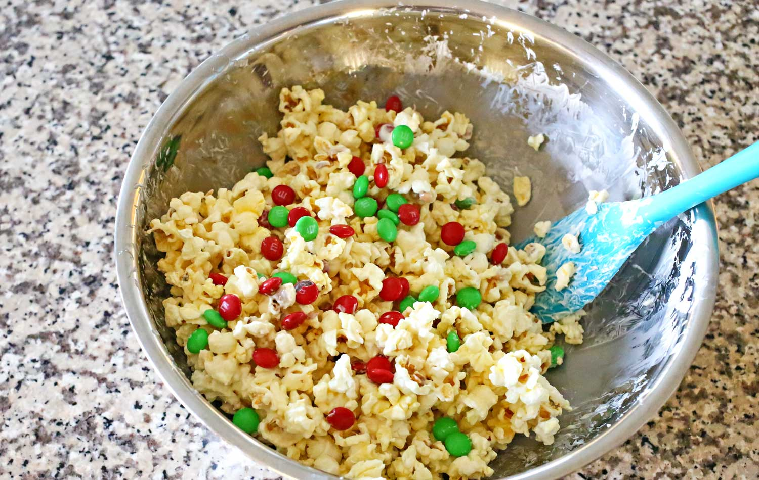 Add the popcorn to a bowl, stir in the white chocolate to coat and then add the red and green M&Ms.