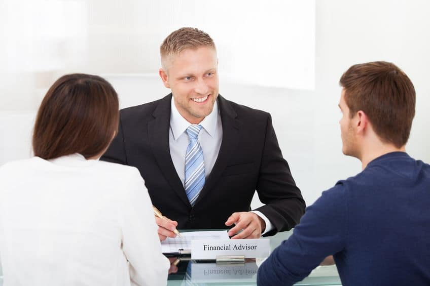 A professional financial adviser assists a couple.