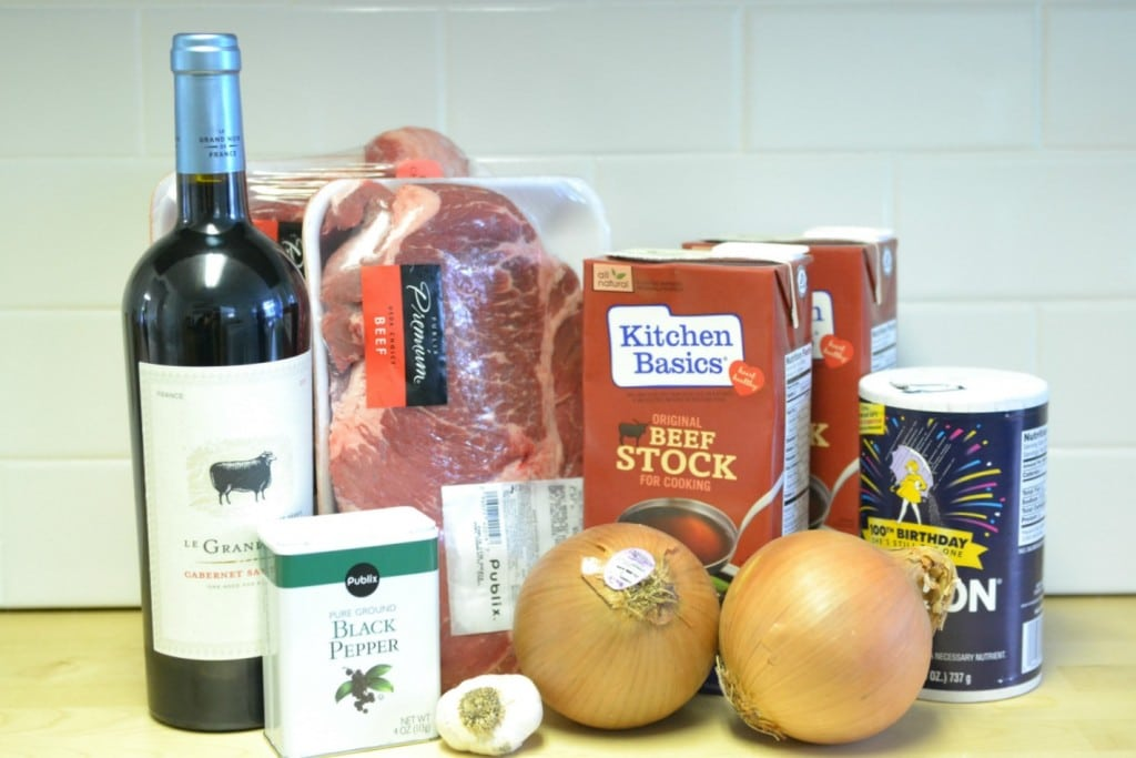 Assemble your ingredients: Chuck roast, red wine, black pepper, onions, beef stock, salt, and baby potatoes.