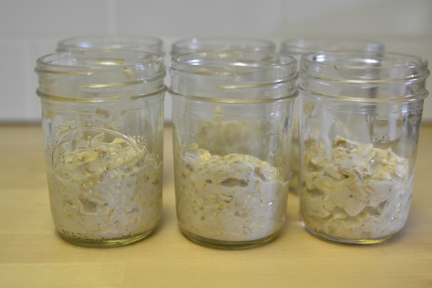 Spoon oatmeal and yogurt mixture into mason jars