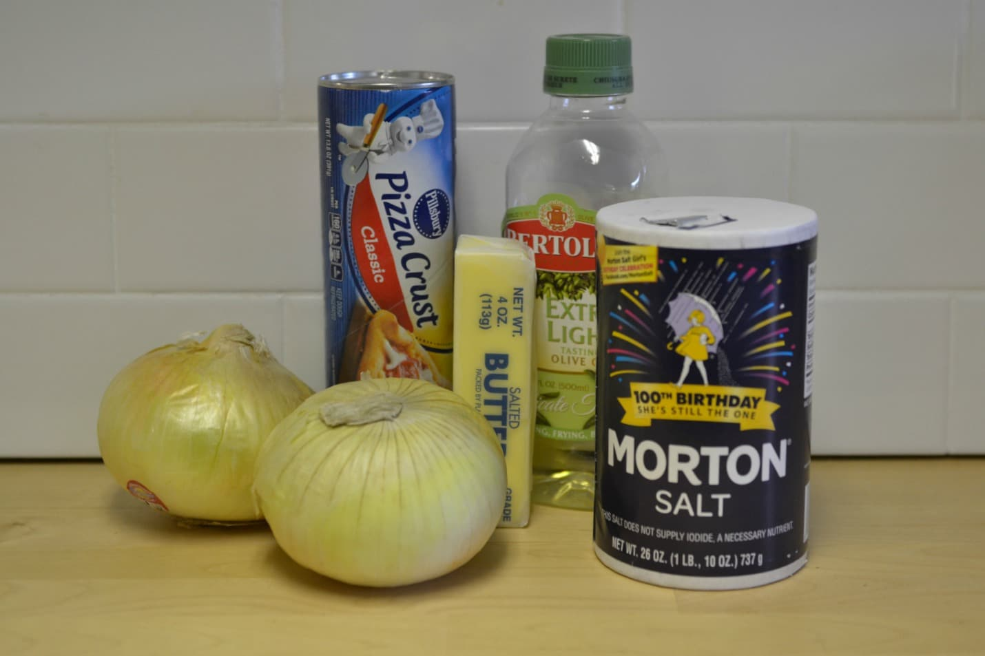 Assemble your ingredients: Refrigerated pizza crust, two sweet onions, butter, olive oil and salt.