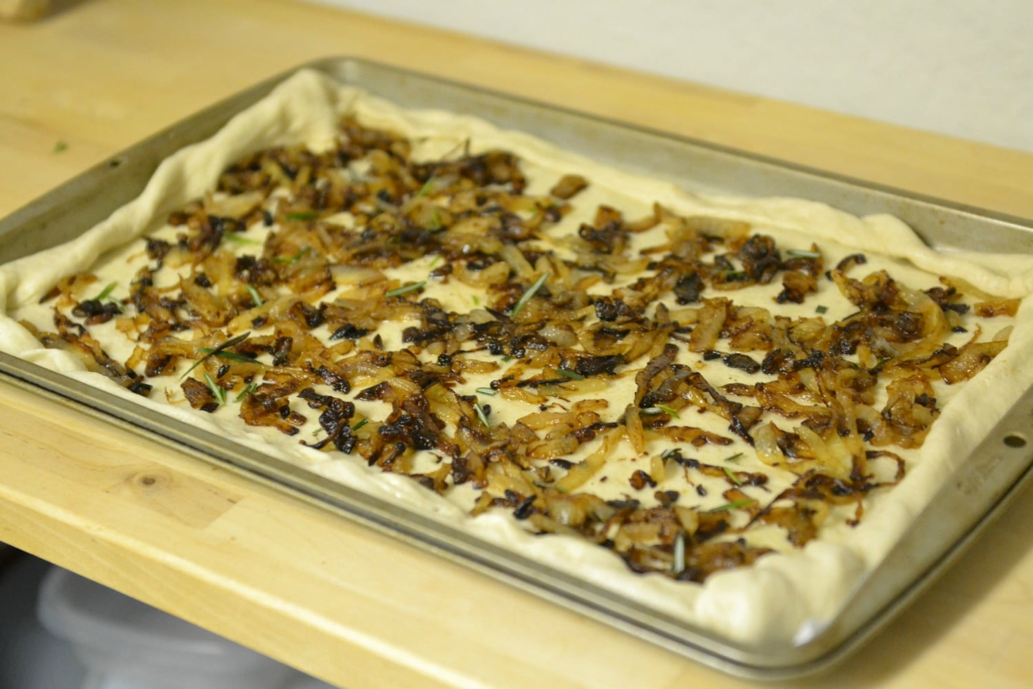Spread caramelized onion over dough. Sprinkle with salt and fresh rosemary, then fold edges over top of onions.