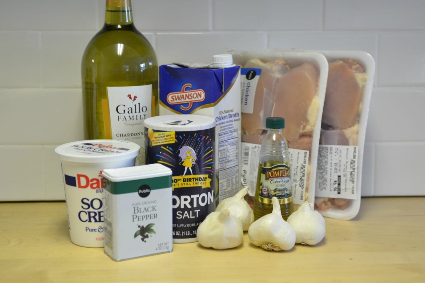 Assemble your ingredients for the garlic chicken including: Olive oil, white wine, chicken broth, sour cream, salt, pepper, boneless skinless chicken thighs, garlic, and fresh thyme.