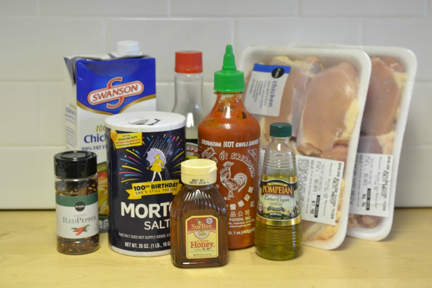Assemble your ingredients: Olive oil, chicken broth, soy sauce, honey, Sriracha sauce, boneless, skinless chicken thighs and red pepper flakes.