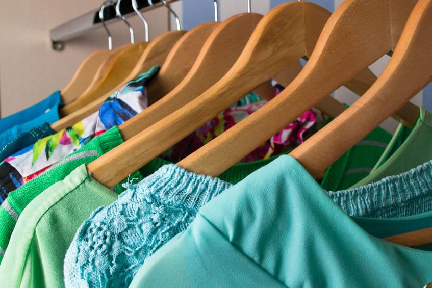 Organize your closet with neat, wooden hangers and color coding.