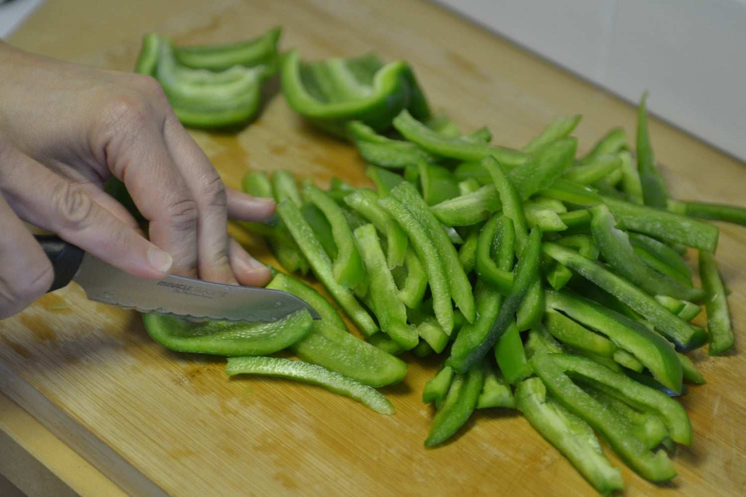 Slice the green peppers into thin strips.