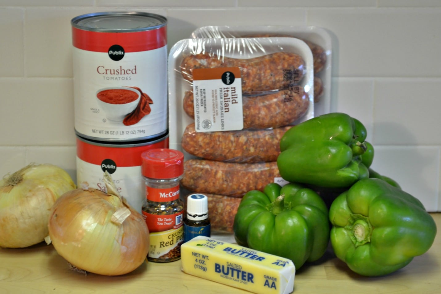 Gather the ingredients for these yummy slow cooker sausage and peppers: onion, tomatoes, spices, butter, peppers and of course, sausage.