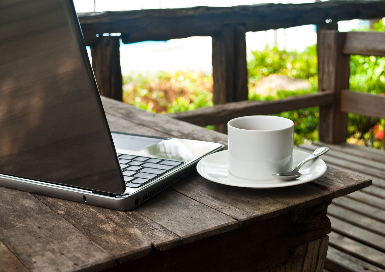 A cup on coffee and a laptop on top of a table outside on a wooden balcony.