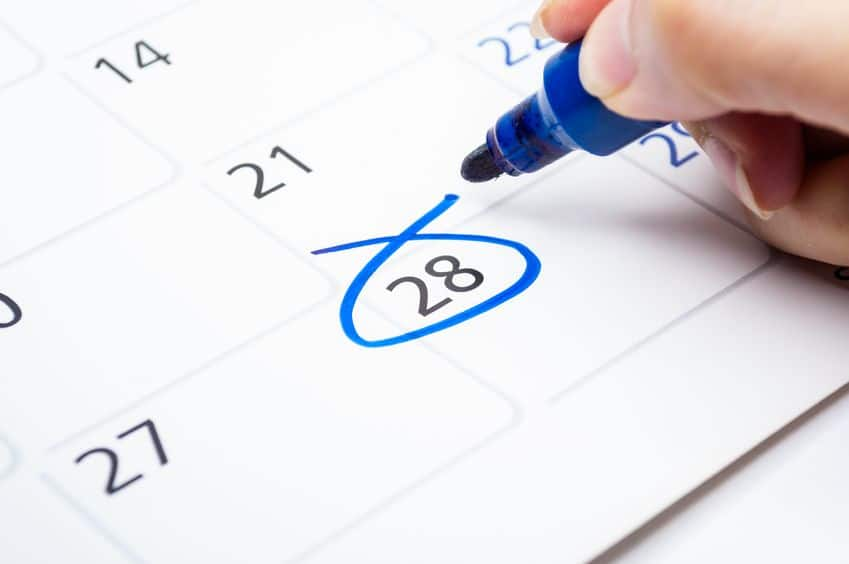 A person circling a date on a calendar.