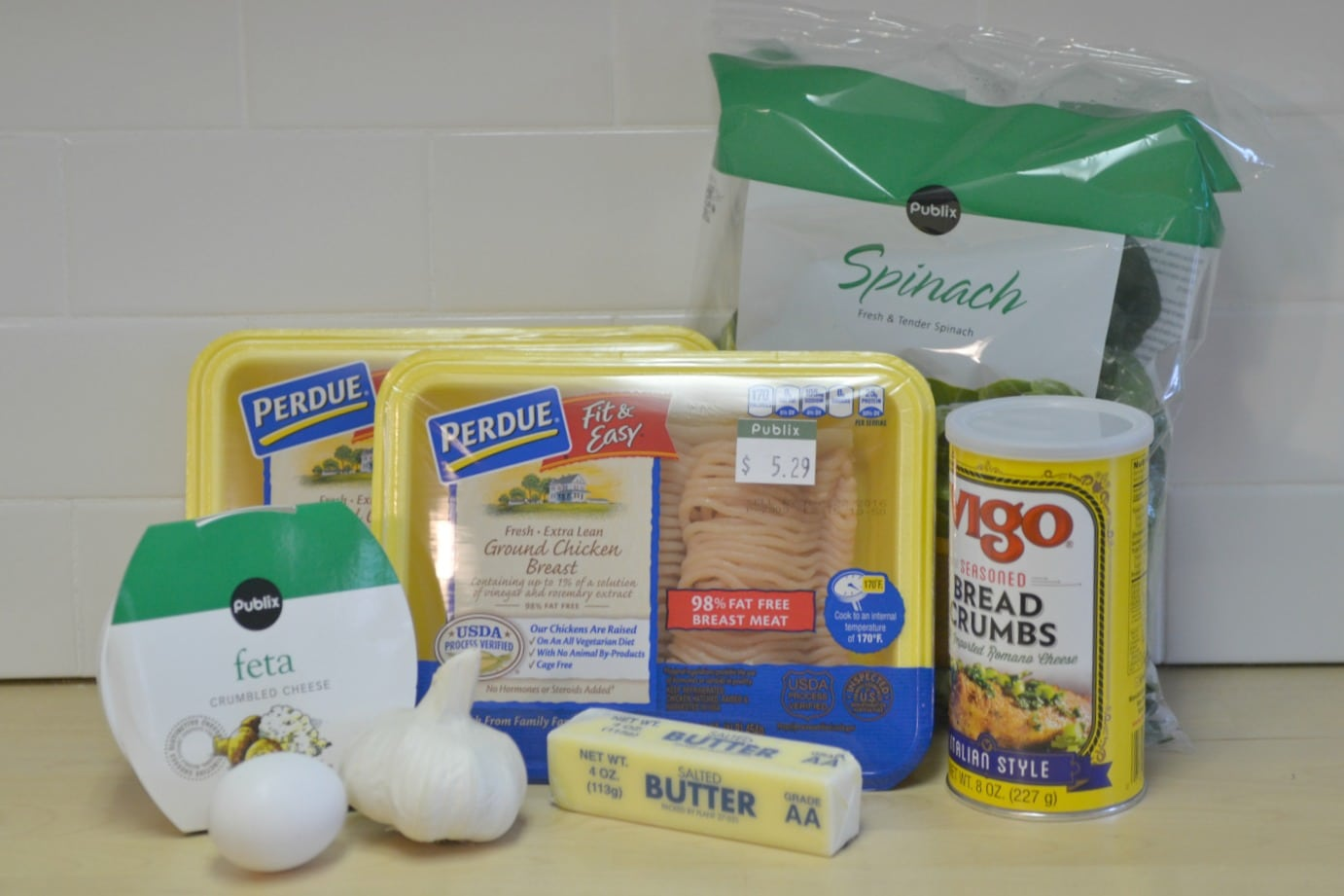 Assemble your ingredients: feta, garlic, egg, butter, breadcrumbs, spinach and ground turkey.