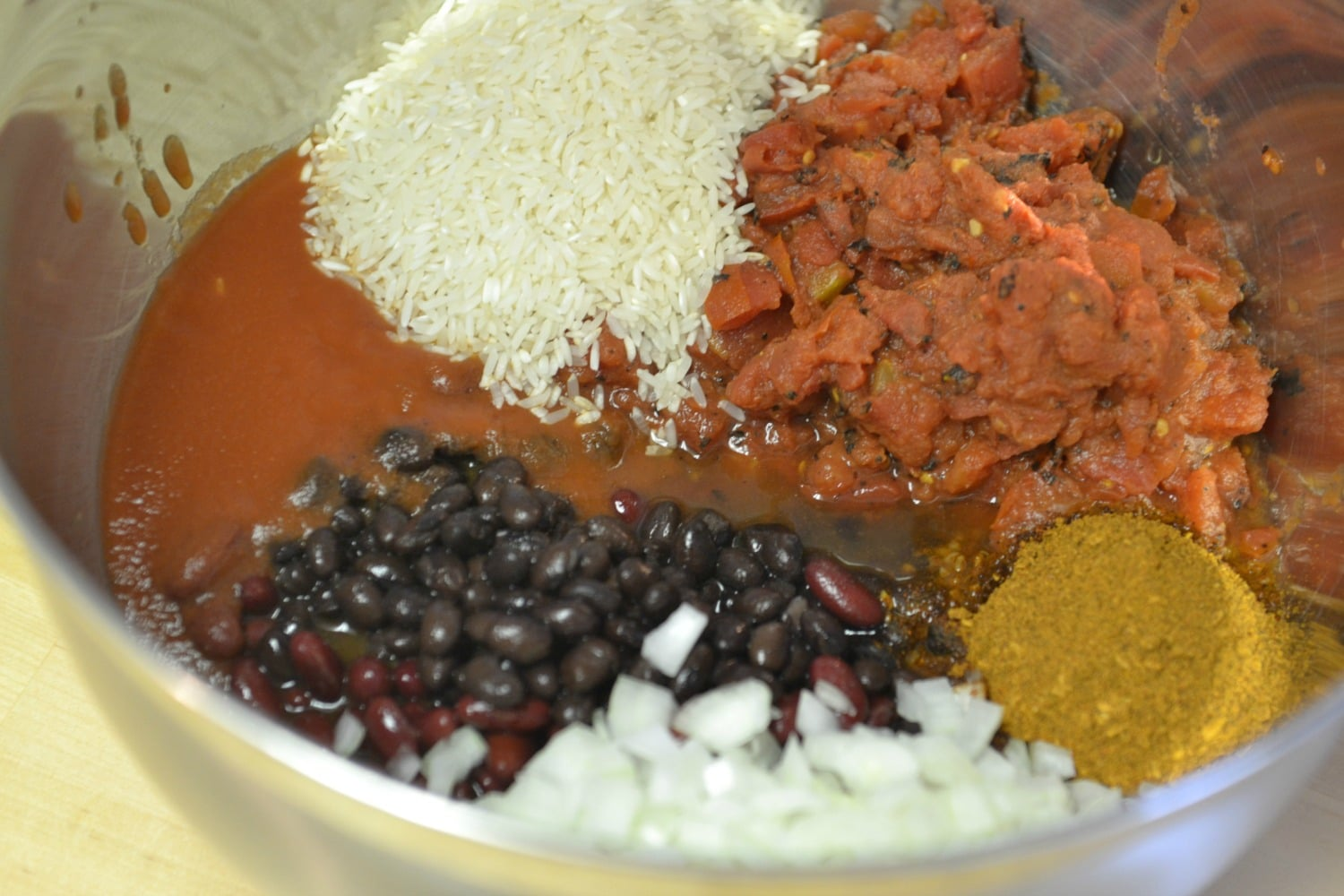 Mix together tomato sauce, beans, seasonings, and rice in a large bowl.