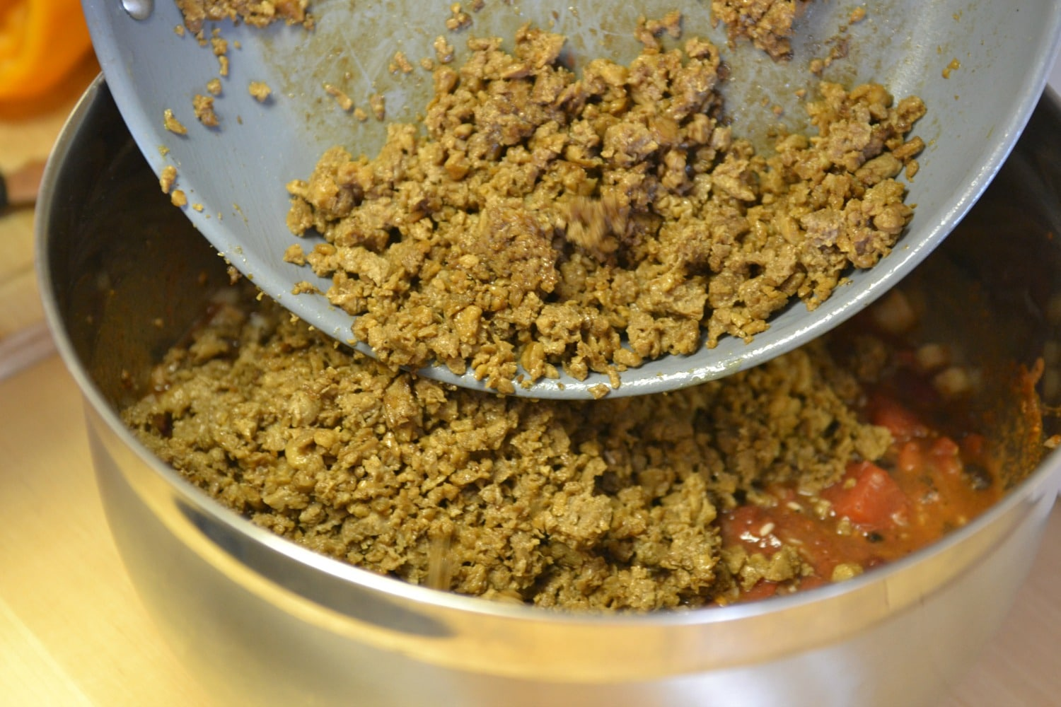 Add the ground beef or vegetarian crumbles into the sauce mixture.