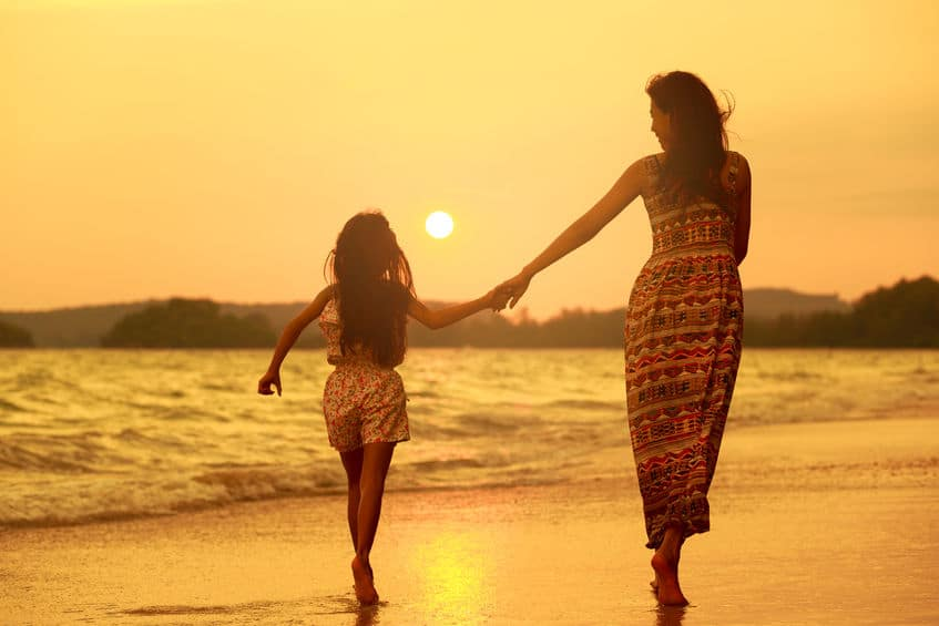A mother and daughter running on the beach as the sun sets.