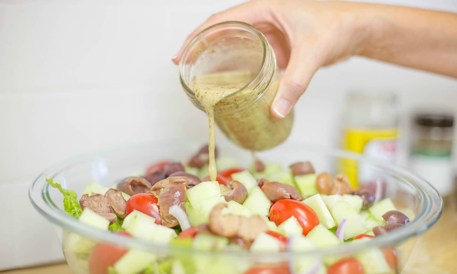 n large bowl; combine lettuce, peppers, tomatoes, olives, red onion, and cucumber . Mix dressing again and toss with salad.
