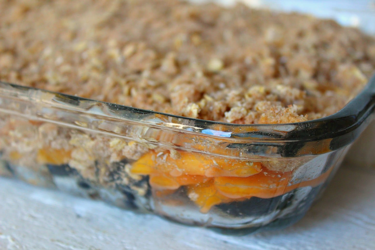 Pour the peaches and blueberries into a shallow glass baking dish and cover with the crumble topping.