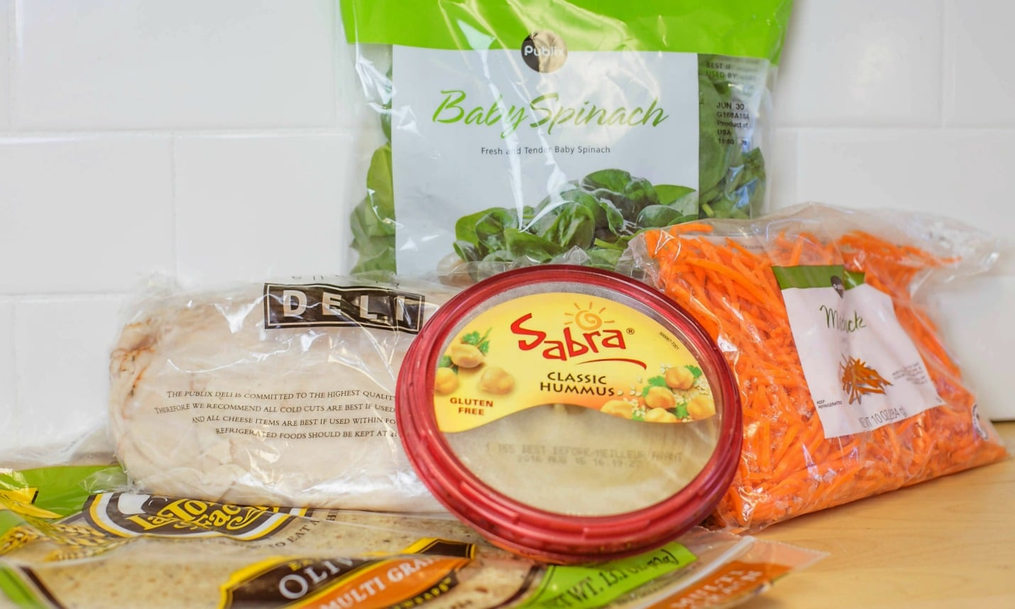 Assemble the ingredients for these quick and easy, make-ahead wraps: deli meat, hummus, spinach, carrots and wraps.