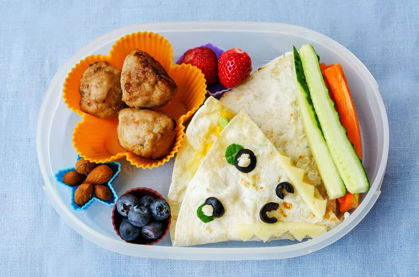 Make healthy foods fun, like this cute bento box lunch with quesadillas and cute cups of fruit and nuts.
