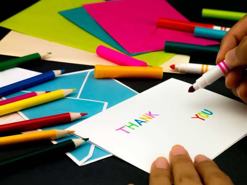 A woman writing a thank you card with colorful markers.