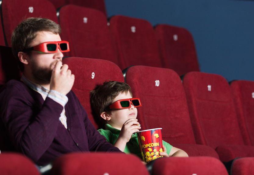 13703302 - a boy with father eating popcorn in 3d movie theater