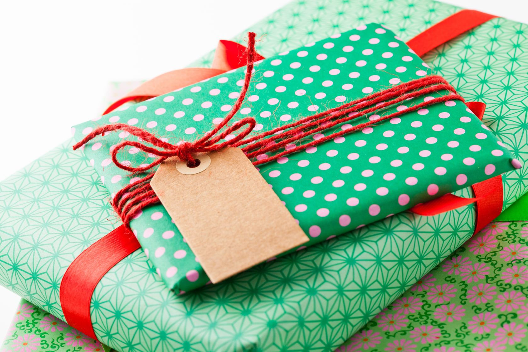16326817 - close up of wrapped gifts with red ribbon and plain cardboard tag on white background