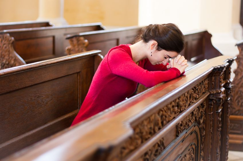 16498655 - young woman praying in a church
