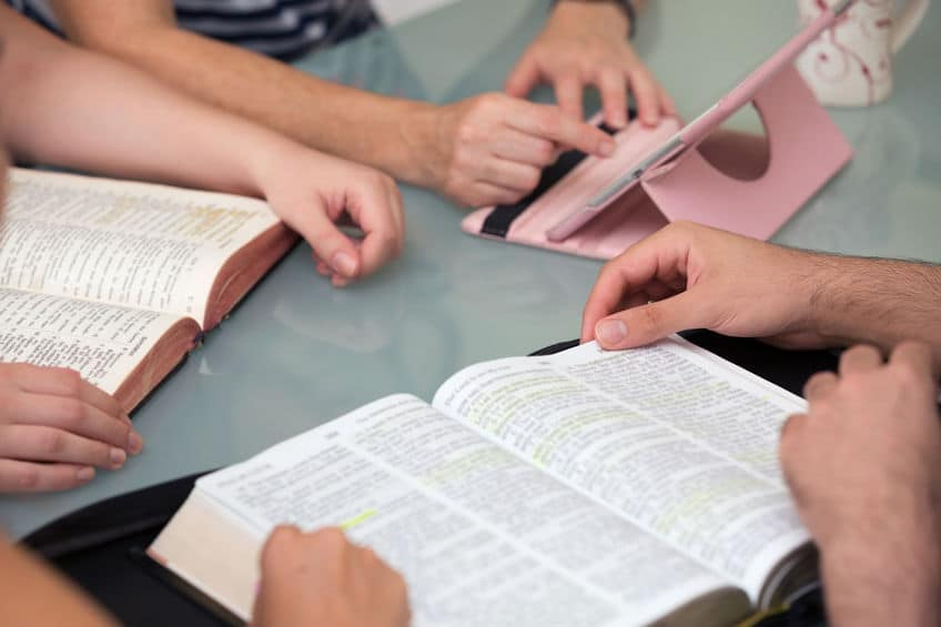 61616302 - close-up of people reading the word of god together
