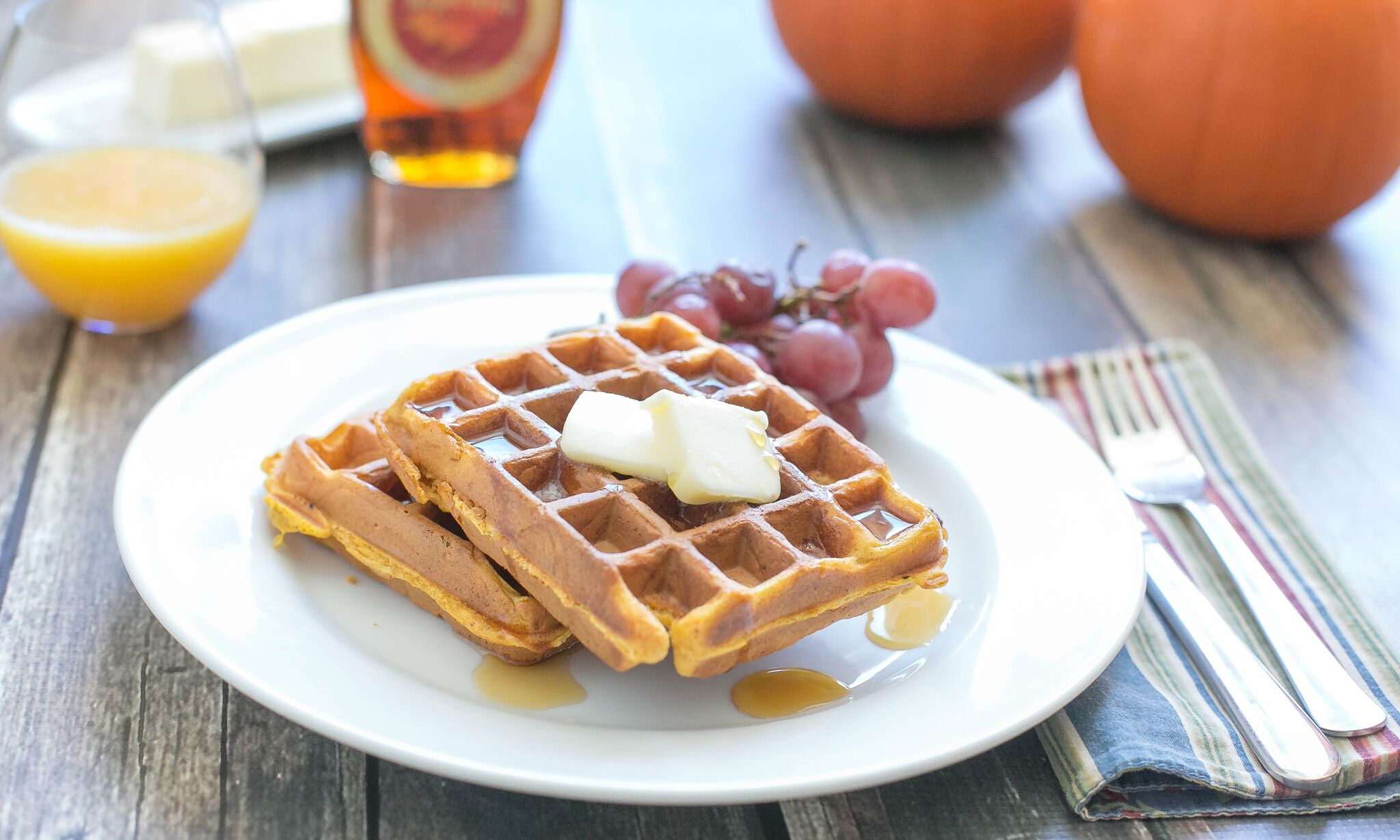 Serve pumpkin waffles with a glass of orange juice and fresh fruit.