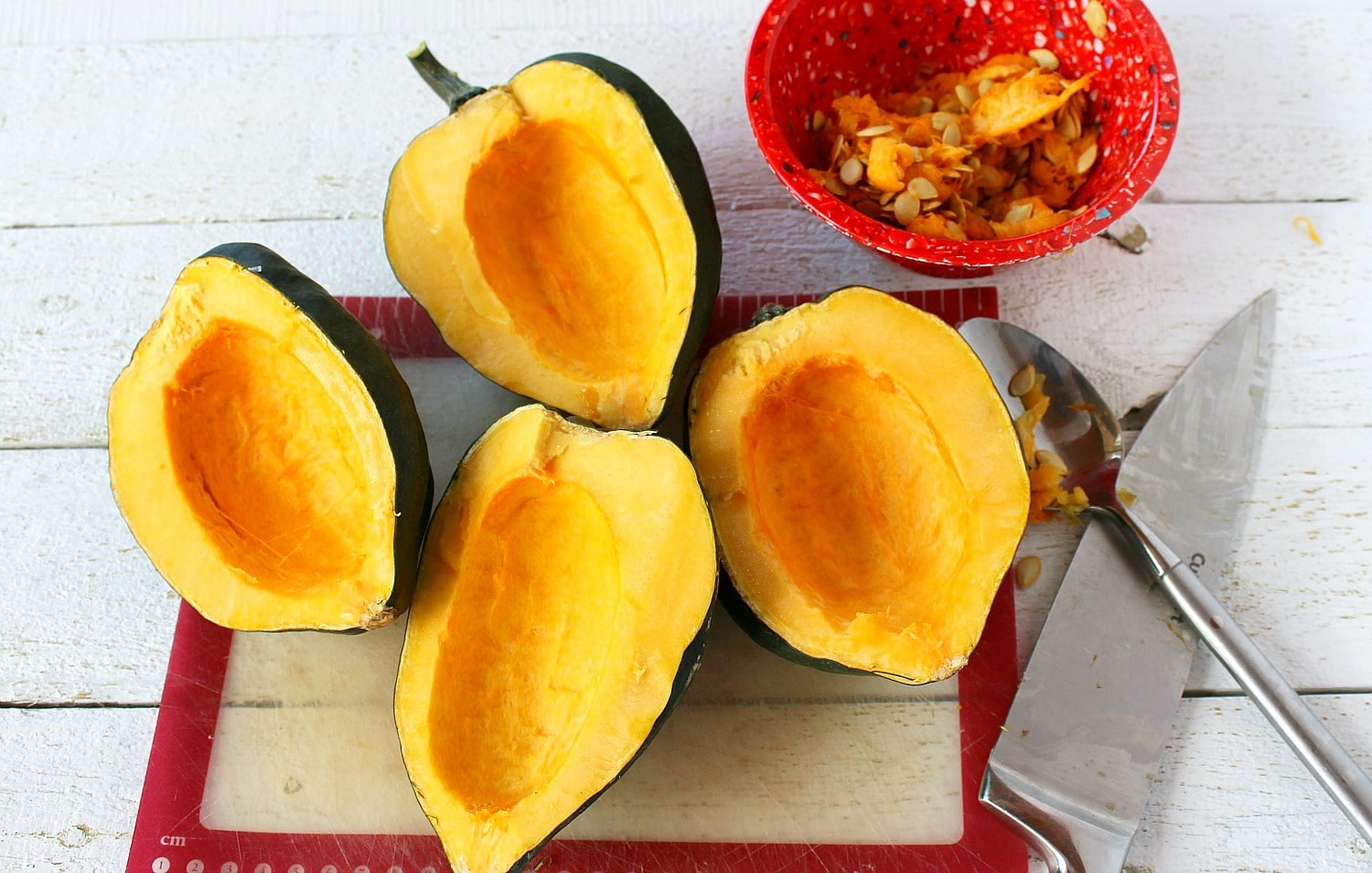 Remove seeds of acorn squash with spoon.