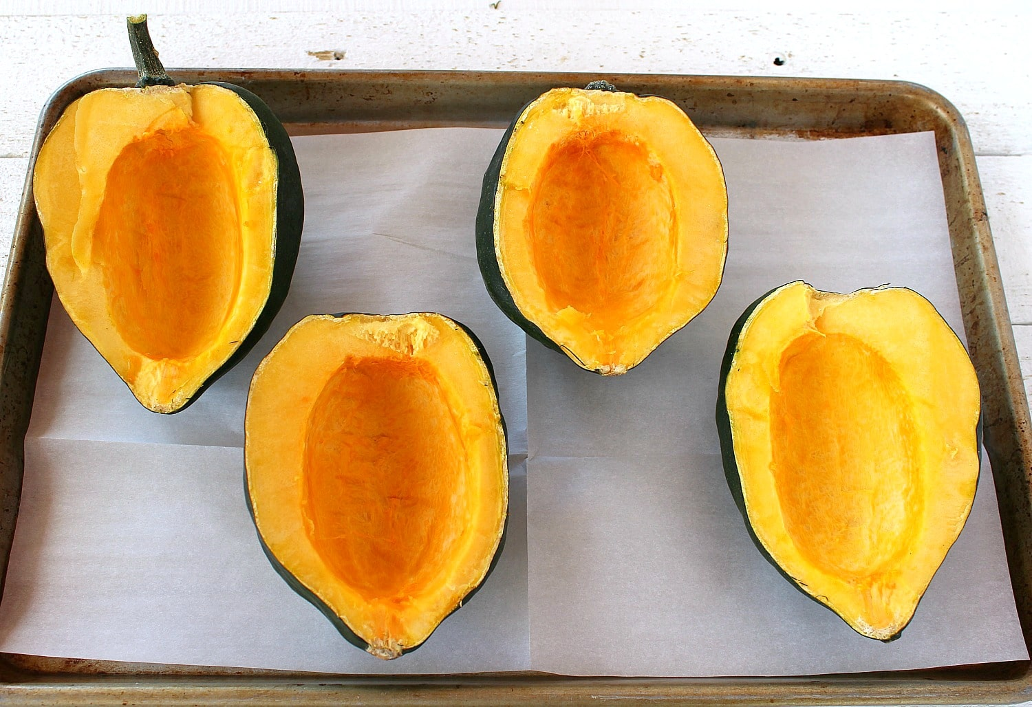 Place each squash flesh side up on cookie sheet with parchment paper.