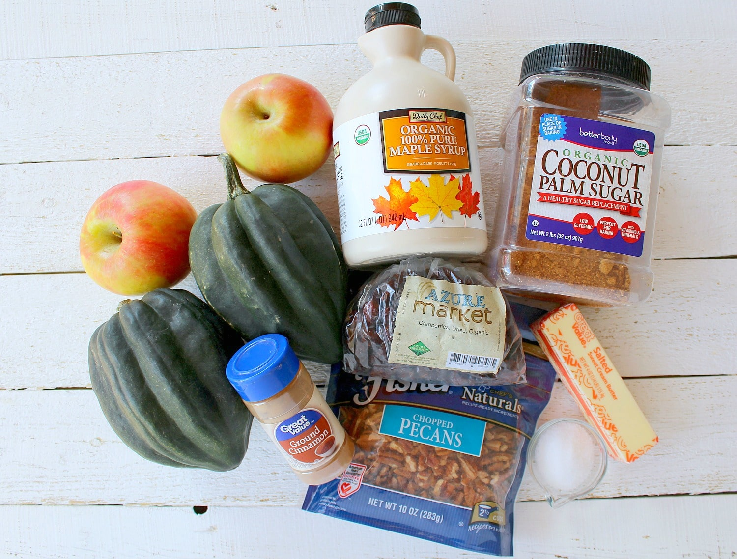 Assemble your ingredients: Acorn squash, apples, pecans, dried cranberries, coconut sugar, butter, maple syrup, cinnamon and salt.