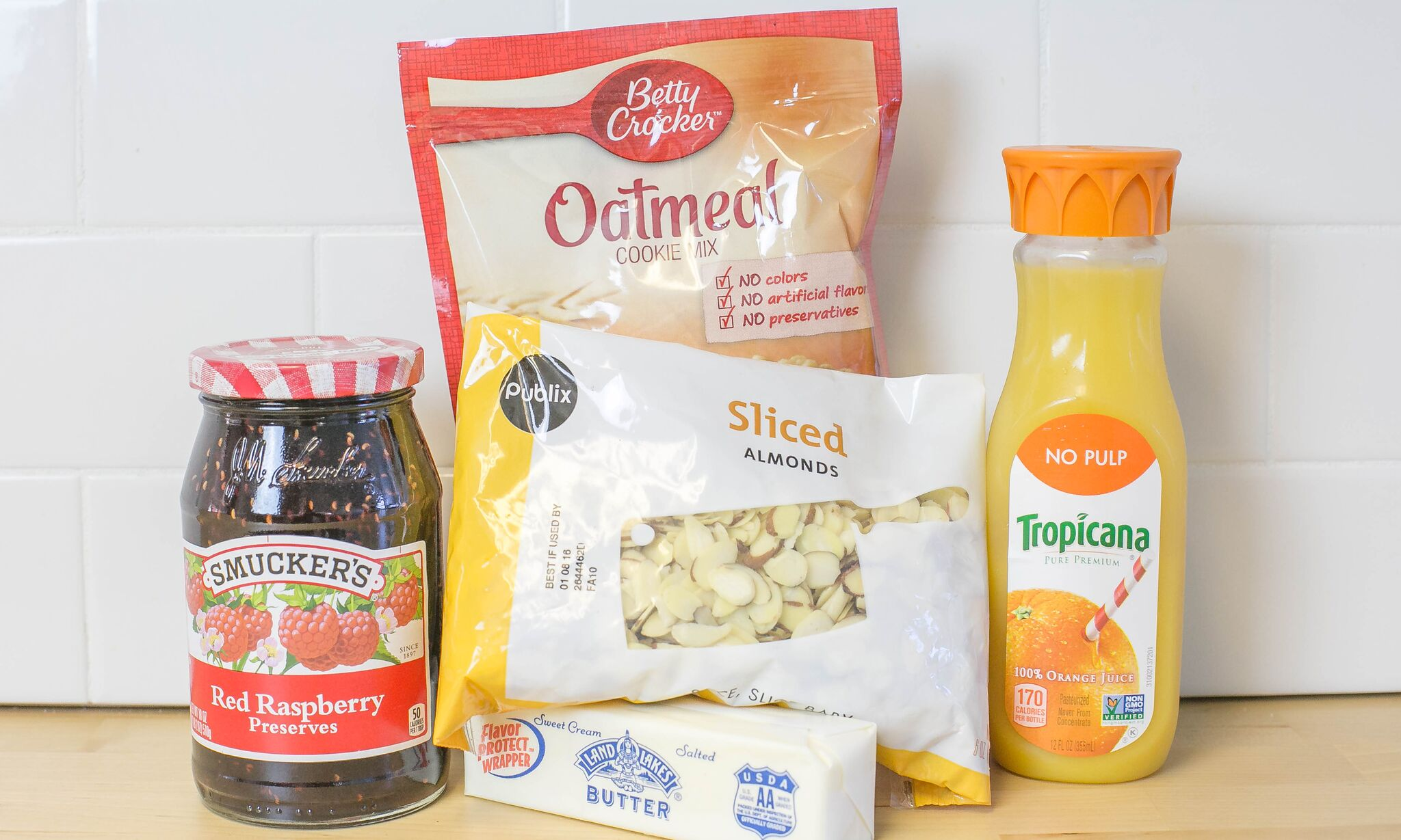 Assemble your ingredients for the raspberry jam crumb bars: butter, sliced almonds, orange juice, and oatmeal cookie mix.