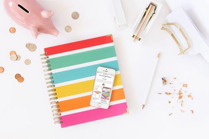A colorful notebook, piggy bank, tape, pencil and smart phone on top of a white desk.