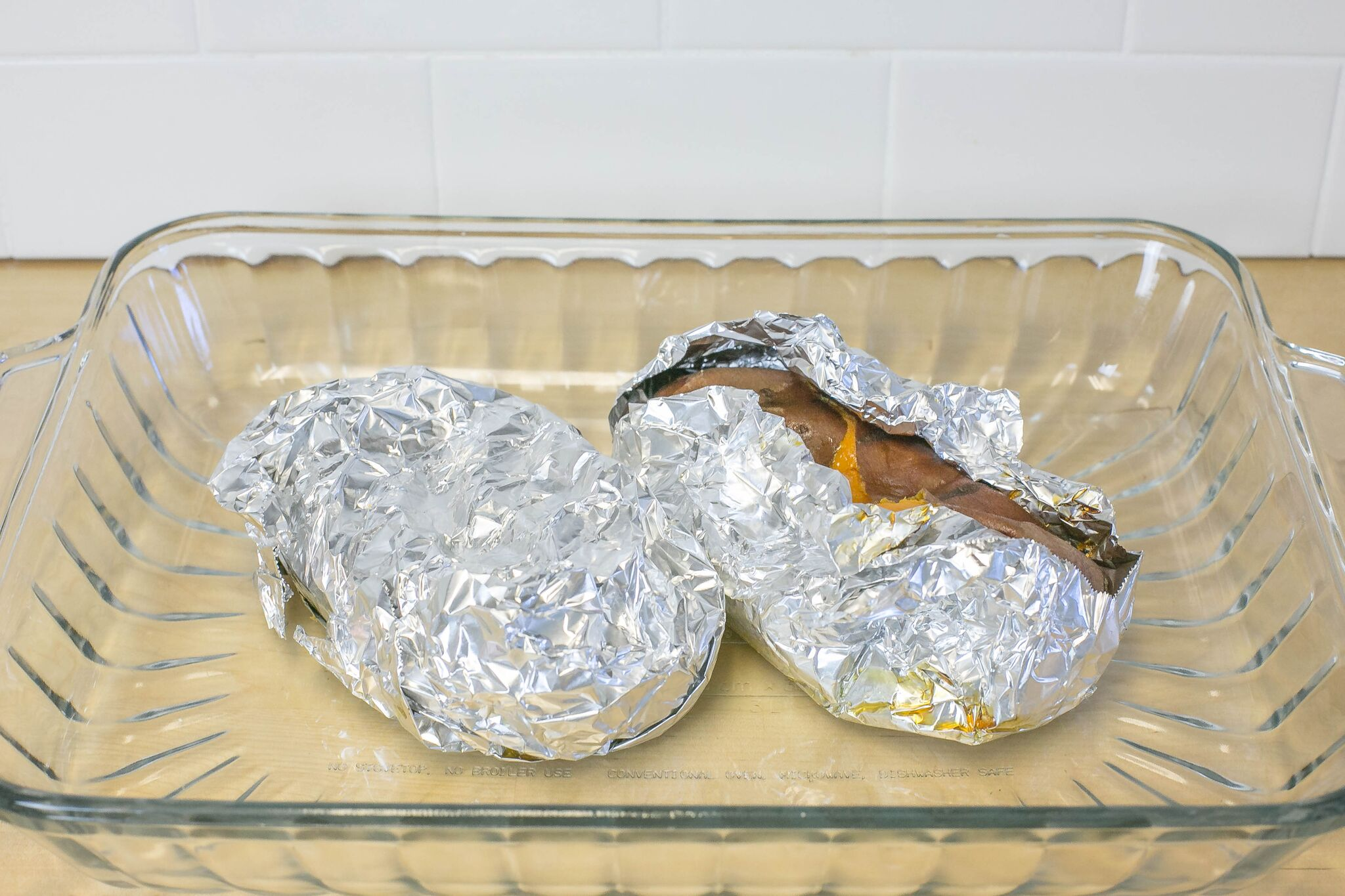 Pierce each sweet potato several times with a fork then wrap potatoes in foil and place in cooking sheet.