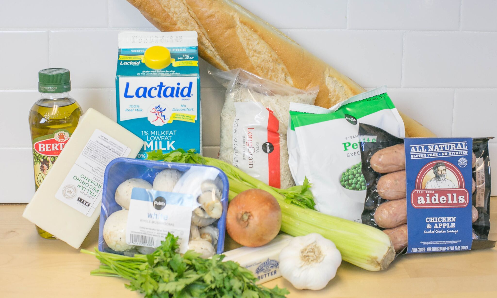 Assemble your ingredients for the rice stuffing: Milk, olive oil, cheese, mushrooms, onions, garlic, frozen peas, rice, bread, sausage, celery, butter and fresh parsley.
