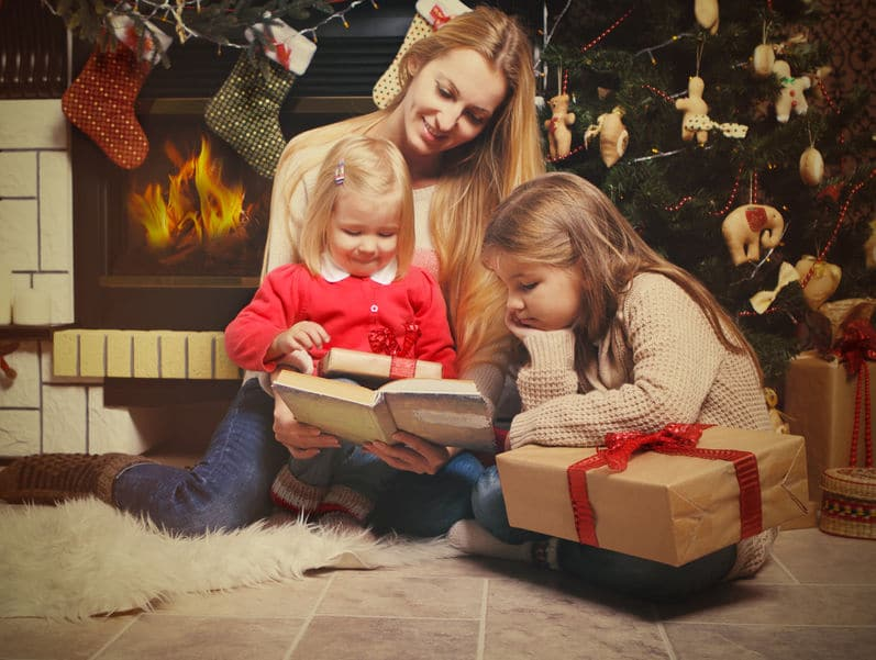 32948637 - young mother and her two little daughters with christmas gifts reading the book by a christmas tree in cozy living room with fireplace in winter