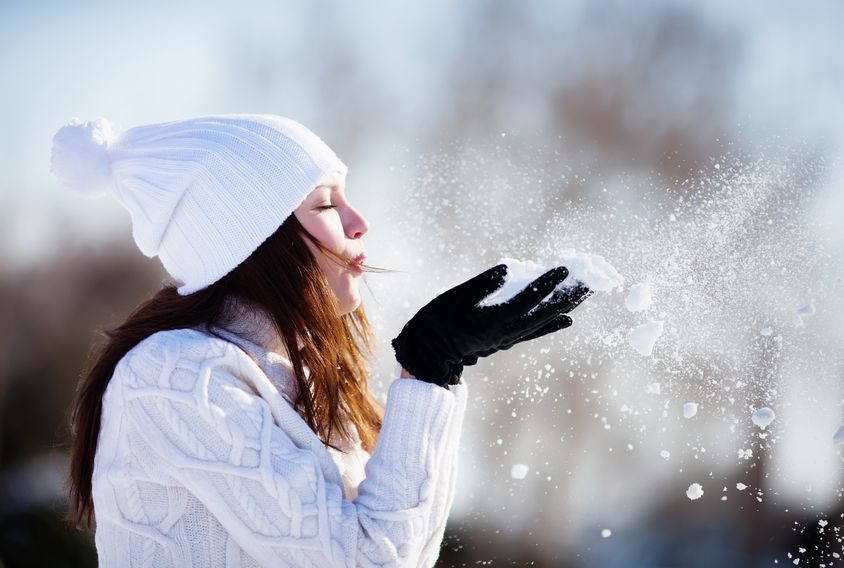 Woman enjoys the winter while blowing snow into the air.