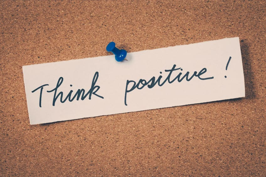 "A ""Think Positive"" note pinned to a cork board."