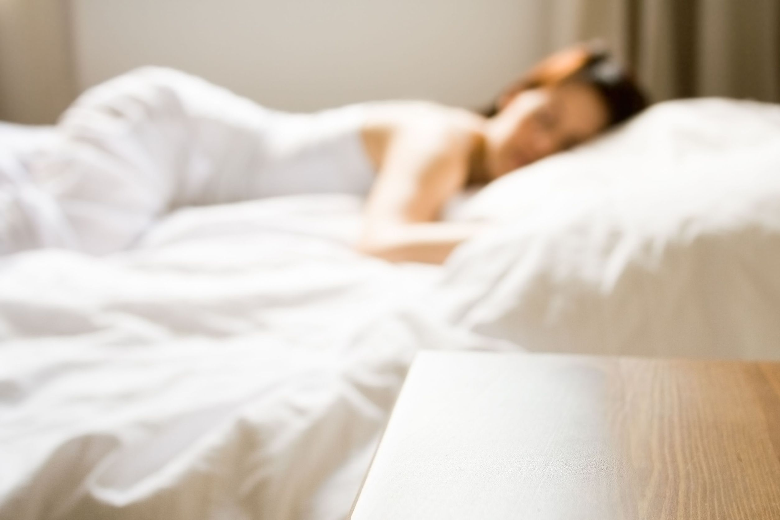 Woman sleeping in a large bed with white white sheets.