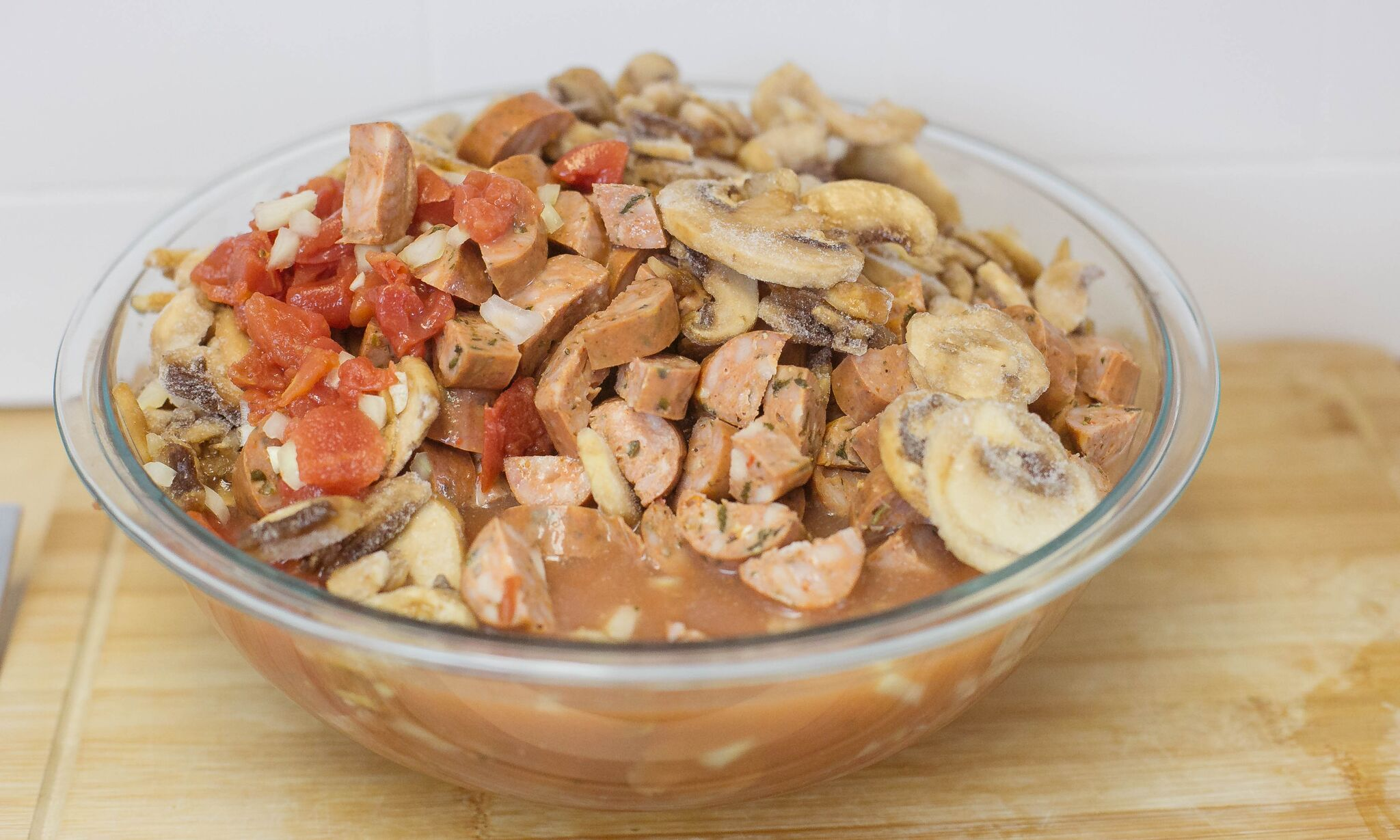 In large bowl, mix together diced tomatoes, sliced mushrooms, onion, garlic, sausage and chicken stock.