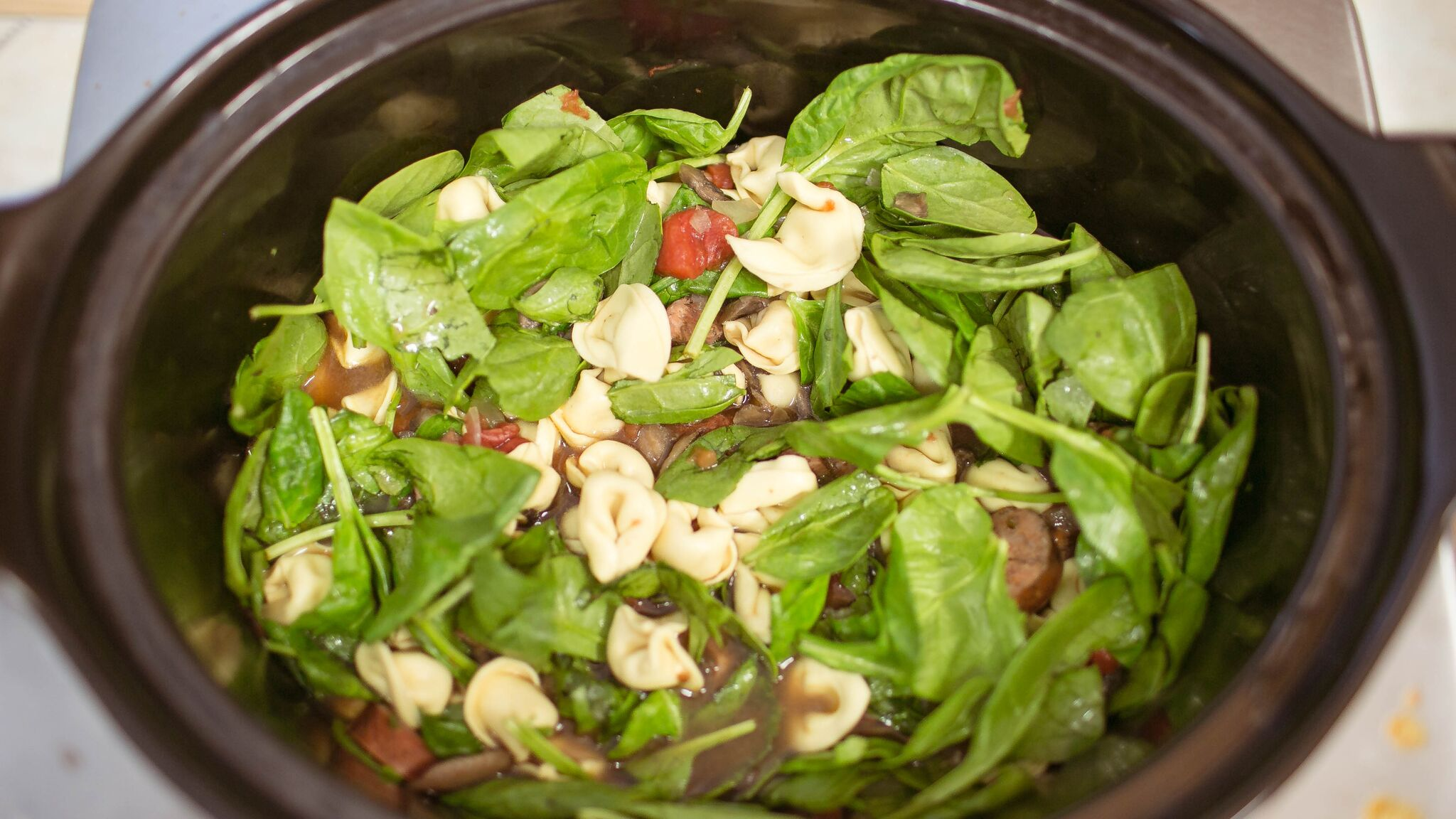 Once you are ready to eat; add package of tortellini directly into crock pot with fresh spinach and stir.