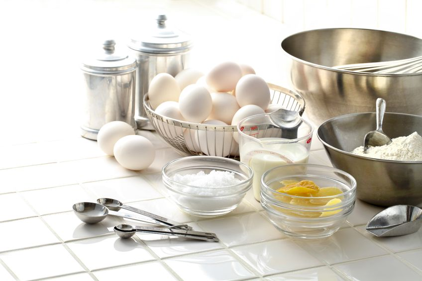 A kitchen counter with various utensils, bowls, a basket of eggs, a measuring cup with milk and other ingredients.
