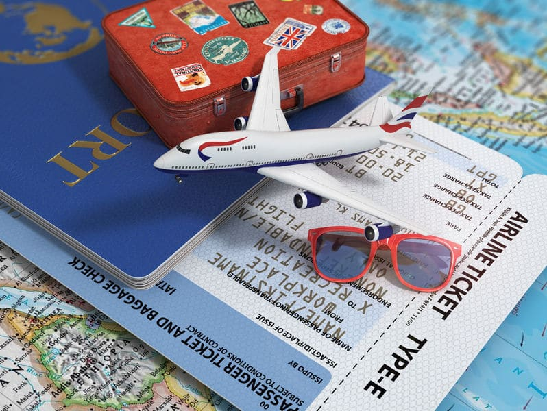 A mini souvenir airplane, suitcase sunglasses on top of a passport, plane ticket and map.