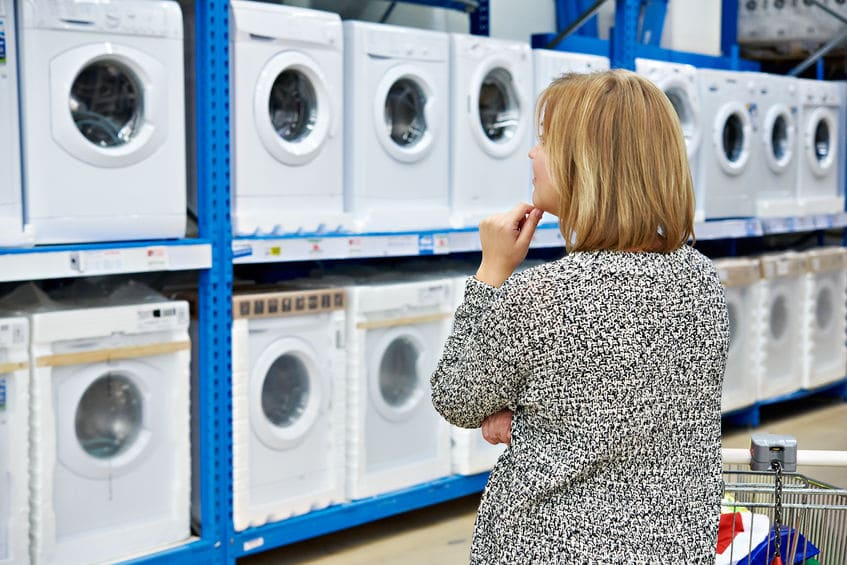 A woman contemplating which washer/dryer appliance to purchase.